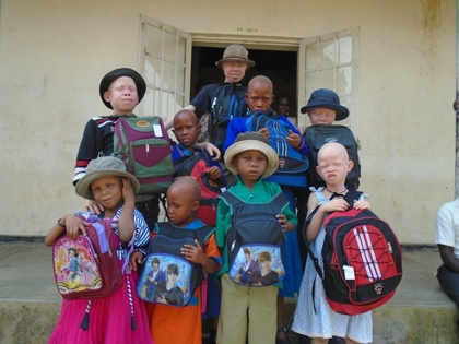 Classic the project albino children posed for a group photograph with their brand new pairs of shoes plus their back packs and some had already received their new set of school uniforms