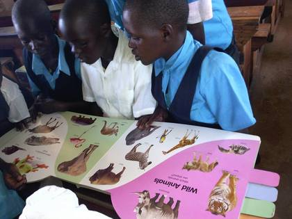 Classic tegot children reading a book  left to right lamwaka patricia  prossy apiyo and akello jacklyn after saturday club