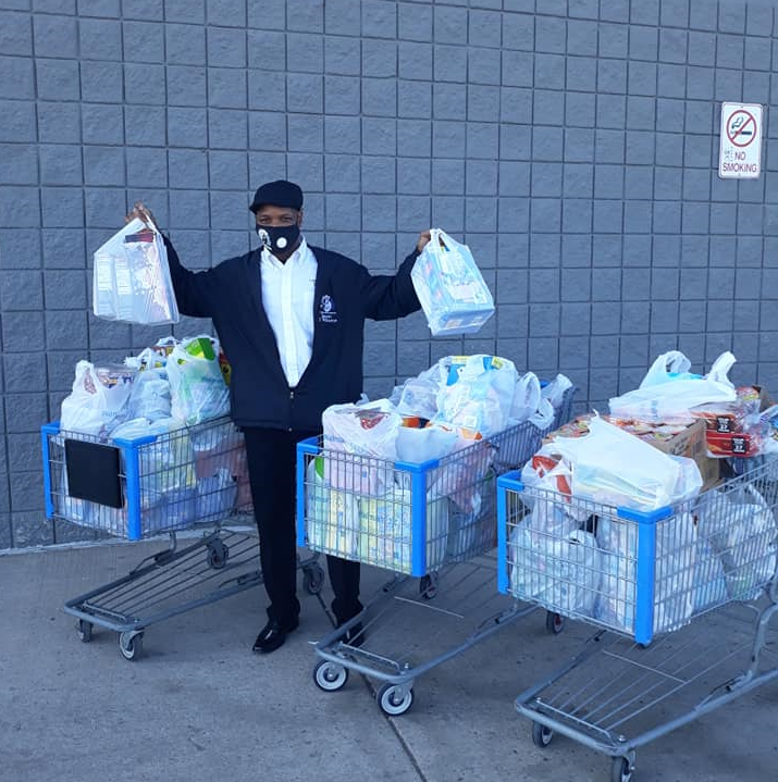 Volunteer buying groceries with gift card to community service workers.